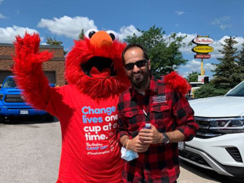 Elmo costume and Volunteer posing for a photo